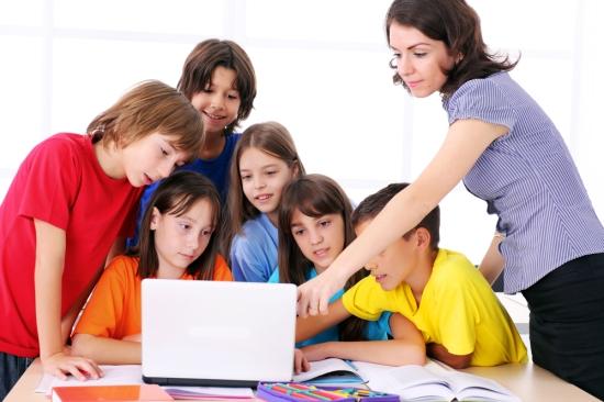 Teacher instructing elementary schoolchildren on using the laptop computer..jpg